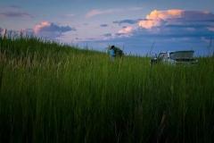 Sabit Aljanov carries reed at sunset in Birlik
