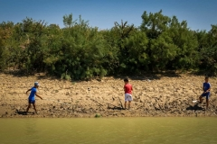 Boys fish by irrigation canal