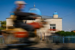 Moped passes by village mosque in Birlik