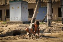 Boy builds castles in the sand by communal water pump